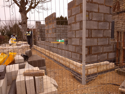 Ext. Day. Pub. East corner, two courses of natural stone walling.