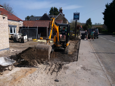 Ext. Day. Pub. The car parking area surface is being compacted in preparationg for resurfacing.