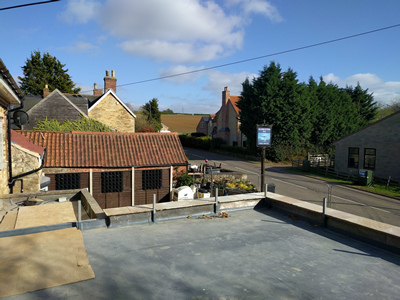 Ext. Day. Pub. The flat roof in progress.