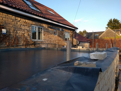 Ext. Day. Pub. A fibreglass and liquid waterproofing process laid onto the flat roof