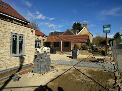 Ext. Day. Pub. The pathway to the main entrance completed.