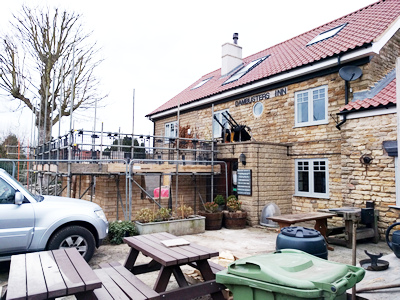 Ext .Day. Pub. Scaffolding erected around the three walls