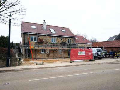 Ext. Day. Pub. Scaffolding erected around the three walls