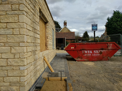 Ext. Day. Pub. The pathway is progressing and cables for the exterior lighting have been fed through the walls.