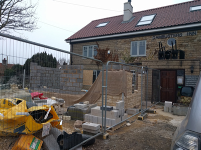 Ext. Day. Pub. Stone walling with window opening, on the East corner.