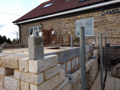 Ext. Day. Pub. The top few courses of stone and block being added to the walls.