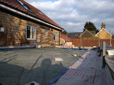 Ext. Day. Pub. The flat roof has been boarded and covered with waterproof membrane.
