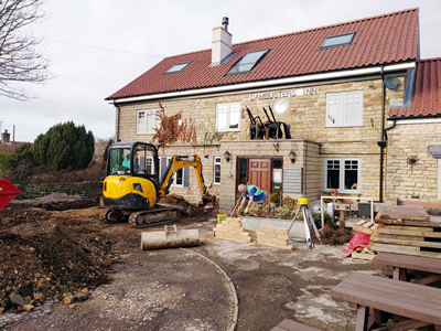 Exterior. Day. Pub with digging machine at work - and sample stonework.