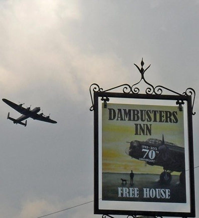 A Lancaster Bomber flies over the pub sign of the Dambusters Inn in Scampton, Lincolnshire. U.K.